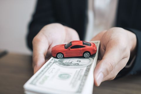 Midsection Of Car Insurance Agent Holding Paper Currency With Toy Car At Office