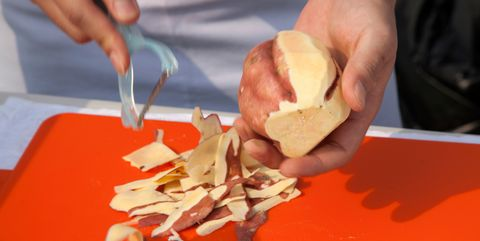 midsection of chef peeling sweet potato on cutting board
