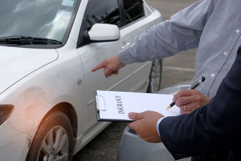 Midsection Of Client And Insurance Agent Standing With Document By Car