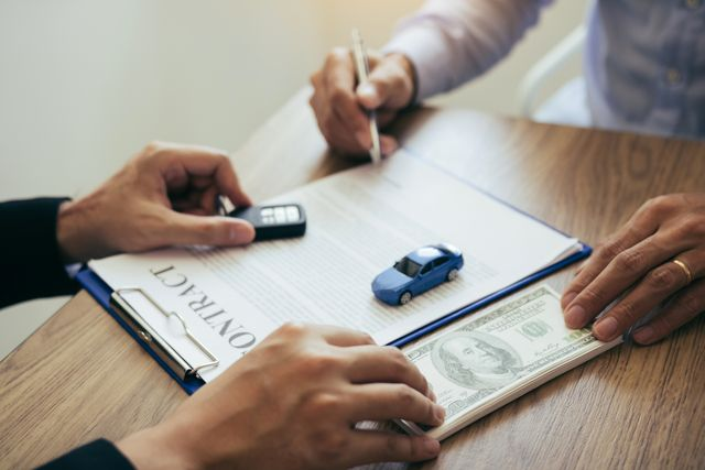 midsection of client giving money to car insurance agent while signing contract at office