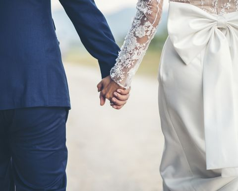 midsection of couple holding hands while walking outdoors
