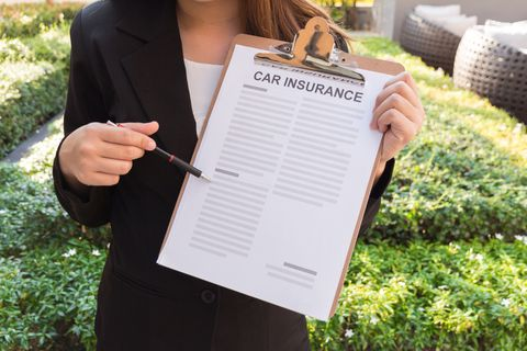 Midsection Of Female Agent With Car Insurance Documents In Yard
