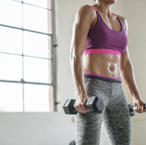 Midsection of female athlete lifting dumbbells in gym