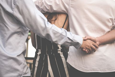 midsection of friends shaking hands with woman