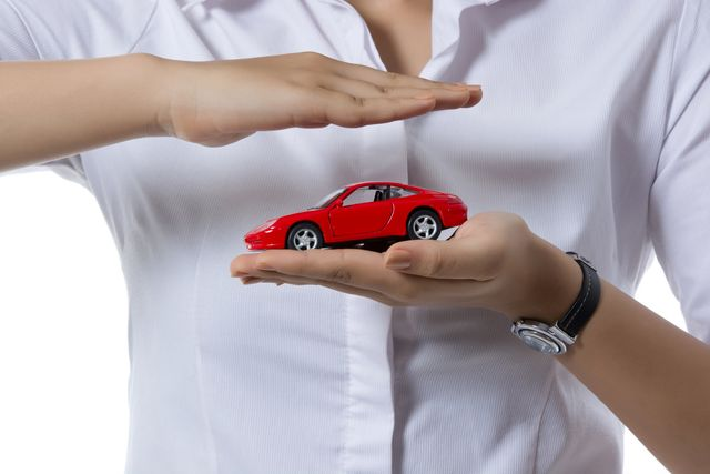 midsection of insurance agent covering toy car against white background