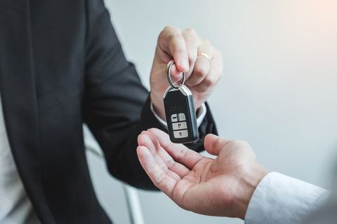 Midsection Of Insurance Agent Giving Key To Customer