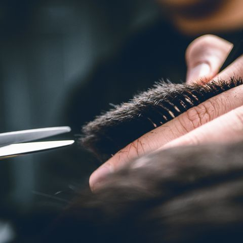 Midsection Of Man Cutting Hair At Barber