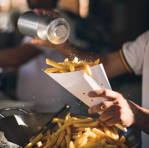 midsection of man dusting salt on french fries