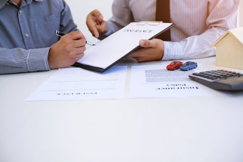 Midsection Of Man Filling Form By Car Insurance Agent At Office