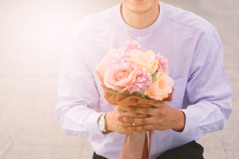 Midsection Of Man Holding Bouquet While Kneeling On Footpath