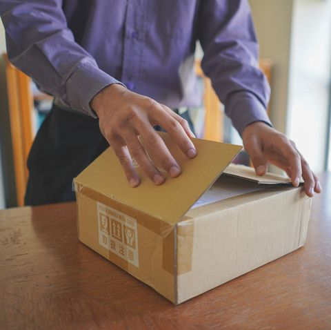 Midsection Of Man Holding Cardboard Box At Table