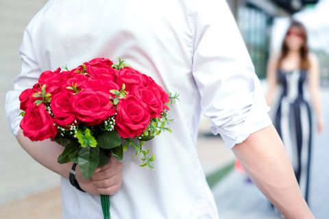 Midsection Of Man Holding Red Roses With Girlfriend In Background