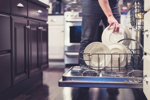 Midsection Of Man Keeping Plates In Dish Washer