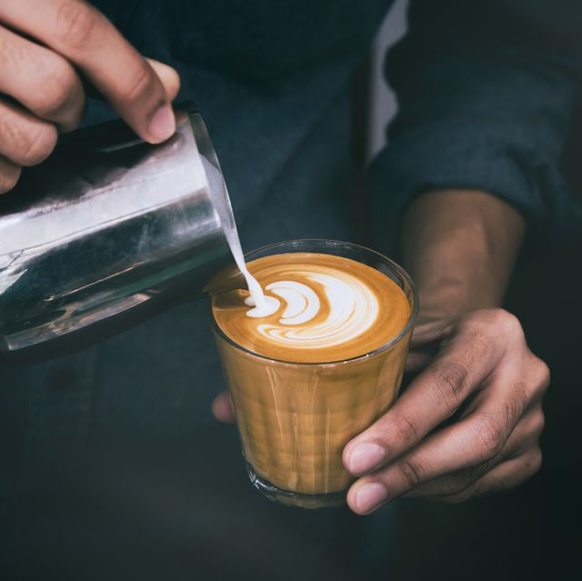 midsection of man pouring milk on coffee