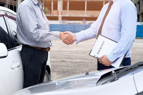 Midsection Of Man Shaking Hand With Insurance Agent By Car
