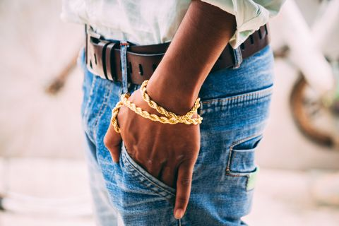 midsection of man with hands in pocket wearing gold bracelet