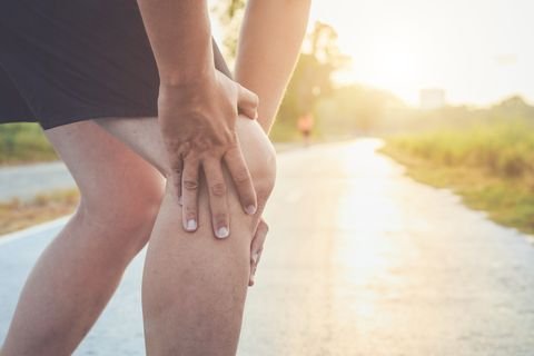 Midsection Of Man With Knee Pain Standing On Road