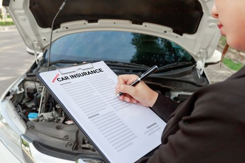 Midsection Of Man Writing On Car Insurance Paper