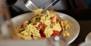 Midsection Of Person Having Scrambled Eggs In Plate On Table