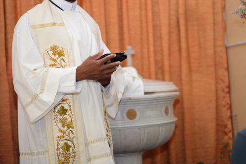 priester bekijkt tablet tijdens de mis
