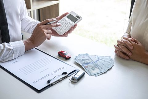 Midsection Of Real Estate Agent Showing Calculation To Customer While Sitting By Table At Office