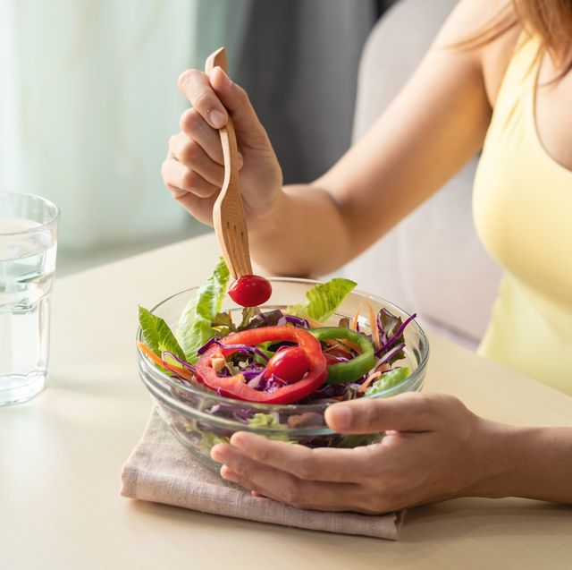 midsection of woman eating salad on table at home