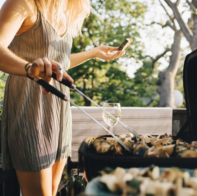 midsection of woman grilling vegetables on barbecue while eating watermelon