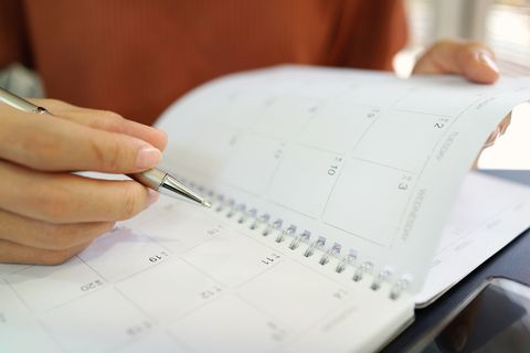 Midsection Of Woman Hand Writing With Pen In Calendar