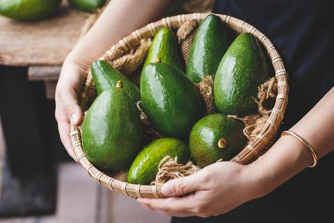 midsection of woman holding avocadoes in basket