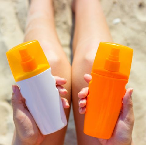 midsection of woman holding bottles while sitting on sand at beach