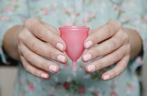 Mujer con copa menstrual en las manos