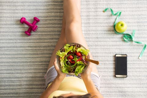 midsection of woman holding salad in bowl while sitting on bed at home