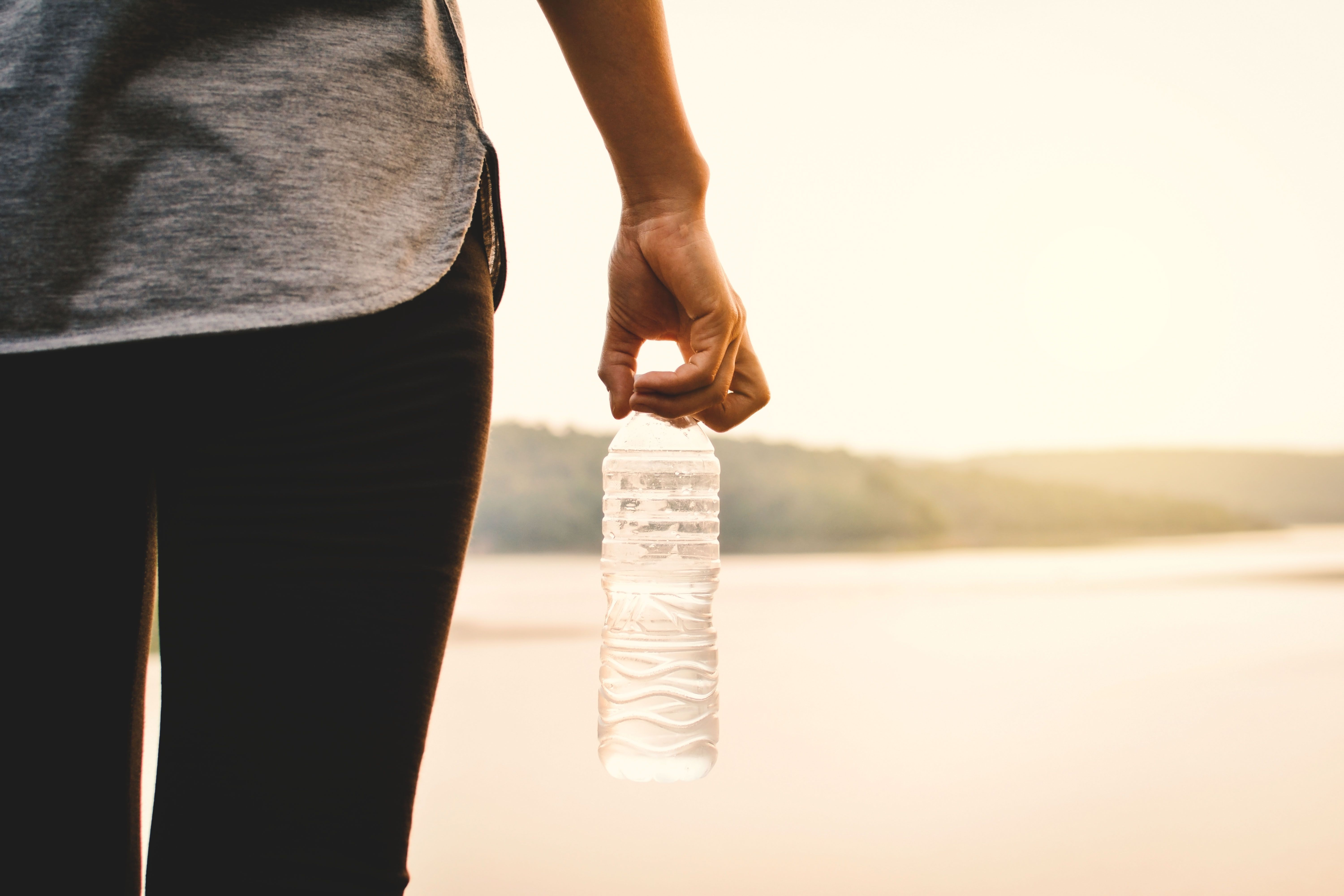 Midsection Of Woman Holding Water Bottle At Beach