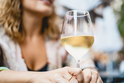 midsection of woman holding wineglass