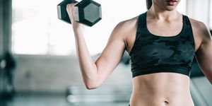 Midsection Of Woman Lifting Dumbbell In Gym