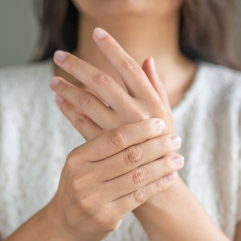 midsection of woman massaging her hand