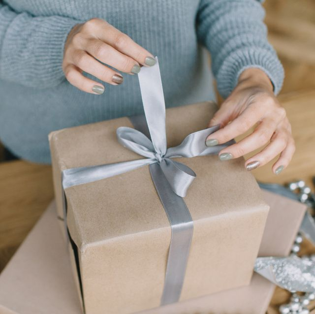 midsection of woman opening gift on table at home