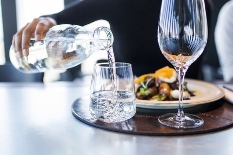 midsection of woman pouring water into glass at restaurant