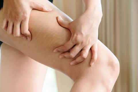 midsection of woman pressing thigh in home