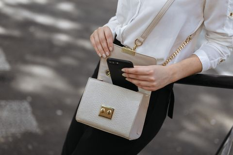 Midsection Of Woman Putting Mobile Phone In Purse While Standing Outdoors