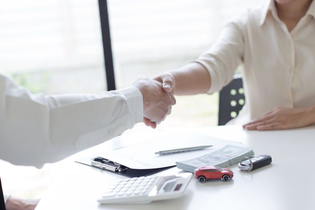 midsection of woman shaking hand with car insurance agent at office