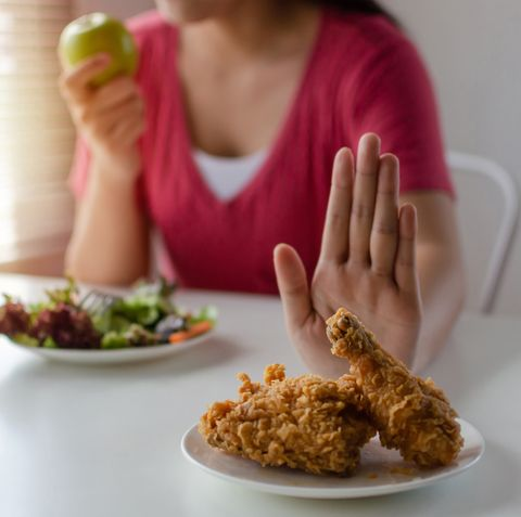 midsection of woman showing stop gesturing to unhealthy food