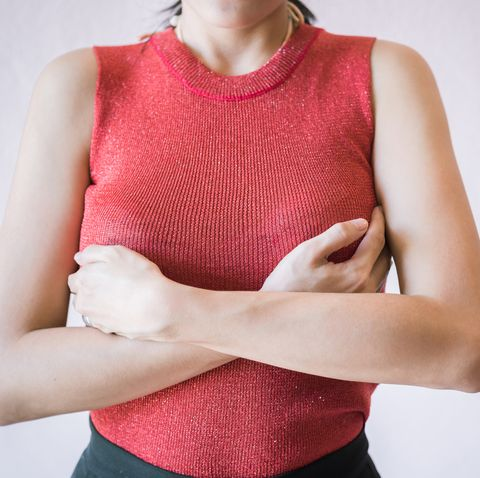 Midsection Of Woman Touching Breast While Suffering From Cancer While Standing Against White Background
