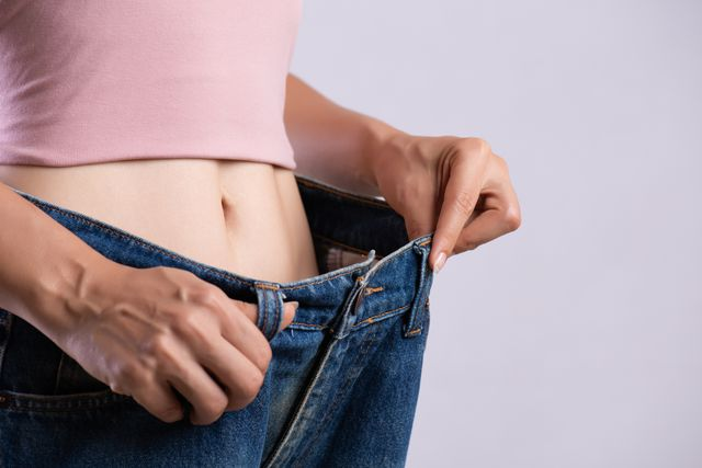 midsection of woman wearing large jeans against white background
