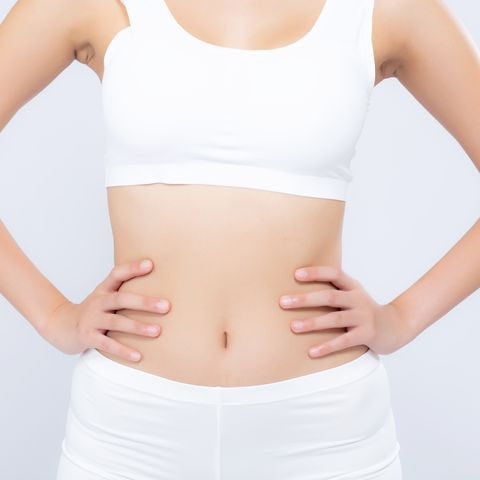 midsection of woman with arms akimbo standing against white background