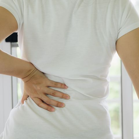 Midsection Of Woman With Backache Against Window At Home