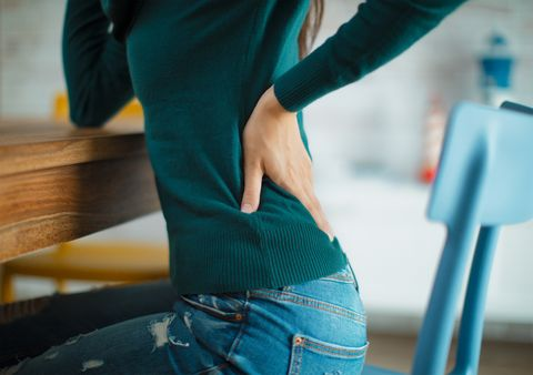 midsection of woman with backache sitting on chair