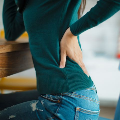 woman dealing with muscle pain sitting on chair