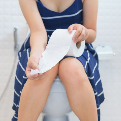 Midsection Of Woman With Paper Sitting On Toilet Bowl