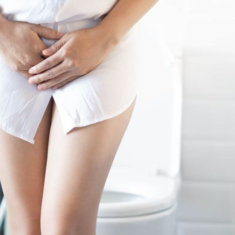 Midsection Of Woman With Urinary Tract Infection In Bathroom At Home